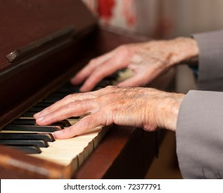 Elderly hands playing on an old harmonium.
