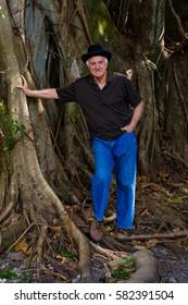 Elderly handsome man outdoor portrait wearing a bowler hat.