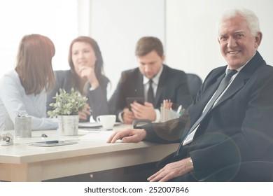 Elderly happy entrepreneur during business meeting