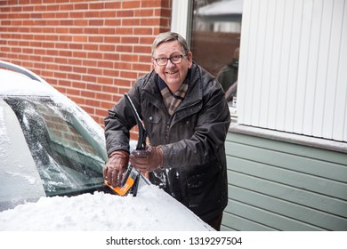 An Elderly, happy man cleaning his car window from snow on a winter day.