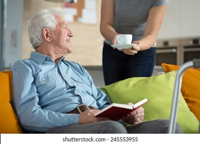 Elderly happy man reading the book and his tea time