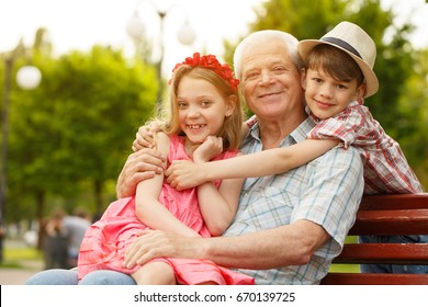 Elderly happy man smiling enjoying resting at the park with his cute little grandkids copyspace family boy girl siblings family bonding leisure holidays happiness nature seasonal retirement concept