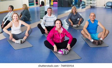 Elderly happy russian  people training in a gym on sport mats