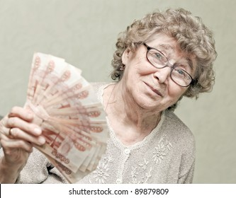 elderly happy woman with pack of money