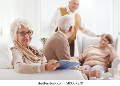 Elderly happy woman reading a book in common room