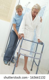 Elderly help keeping an elderly woman secure as she ambulates from  with his walker. On a white background.