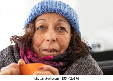 An elderly homeless woman with a cup of soup , social problems like homelessness problem concept