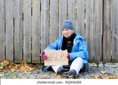 Elderly homeless woman sitting on a cobbled sidewalk with a hand written sign - Help - on hardboard