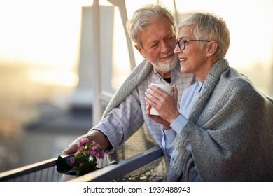 Una pareja de ancianos abrazados y enamorados pasan un maravilloso rato juntos mientras disfrutan de una hermosa puesta de sol desde la terraza en un ambiente relajado de su apartamento. Relación, amor, juntos