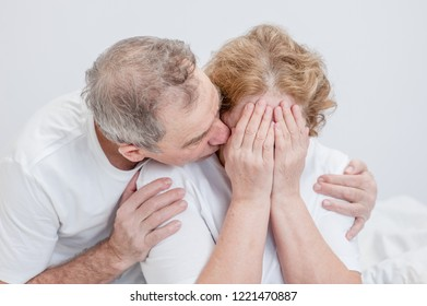an elderly husband calms a crying wife