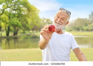 elderly husband wearing sunglasses and white shirt is giving apple to someone in the park during summer time (healthy concept)