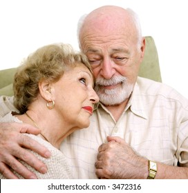 An elderly husband and wife consoling themselves over the loss of a loved one.