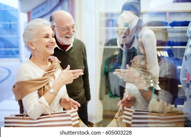 Elderly husband and wife looking at shop-display with modern casualwear
