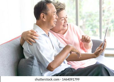 Elderly husband and wife sitting together on sofa at home and enjoy using tablet.