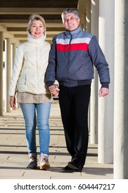 Elderly husband and wife are walking together clear sunny day between columns