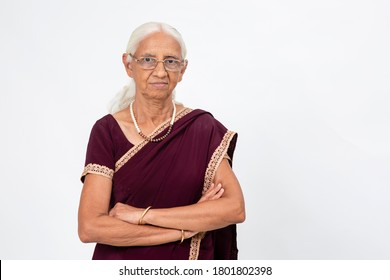 Elderly Indian woman wearing spectacles stands with her arms folded. Senior woman with a serious expression looking into the camera