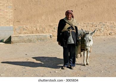 Elderly iranian shepherd with a donkey
