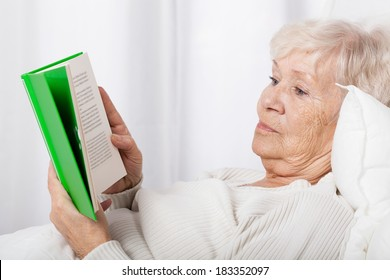 Elderly lady during reading book in bed