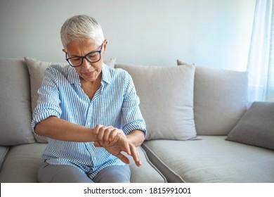 Elderly lady is enduring strong ache. Elderly woman suffering from pain in hand, closeup. Elderly female is expressing pain. Woman suffering from pain From Rheumatoid Arthritis
