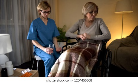 Elderly lady feeling homesick refusing to take medicine from nurse hands sadness