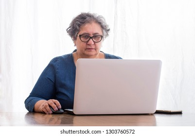 7f0b594faa The elderly lady with glasses intently browses the internet content on a  laptop - on the