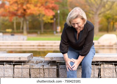 Elderly lady grabbing her knee in pain as she sits on a wall surrounding a pond after injuring herself out walking on an autumn day with copy space