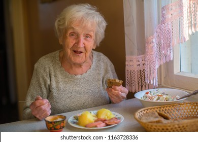 An elderly lady has dinner sitting at the table at home.