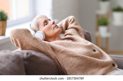 Elderly lady in headphones lying on couch and listening to music with closed eyes while resting in cozy living room at home
