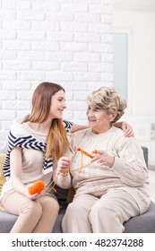 Elderly lady knitting with orange wool, with her granddaughter hugging her