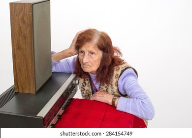 Elderly lady listening attentively to the old radio.