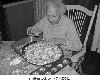 Elderly lady Mother, sitting at a table in old chair, making home made ravioli for the family dinner. Traditional Italian food.