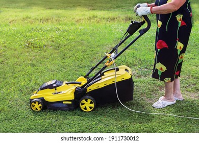 Elderly lady pushing an electric mower to cut the grass. Active seniors are passionate about their hobbies and lead meaningful quiet lives