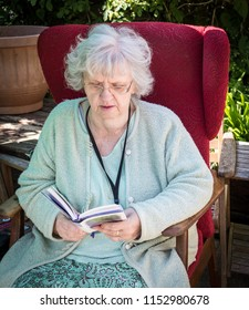 Elderly lady reading in the back garden