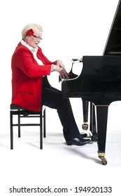 elderly lady in red playing the grand piano in studio with white background