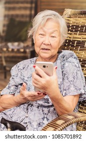 Elderly lady seated at home learning how to use the smartphone. Obaasan (grandma), japanese descendant.