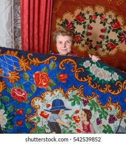 Elderly lady is showing her handmade print carpet in punchneedle embroidery technique in carpeted home interior in Ukraine.