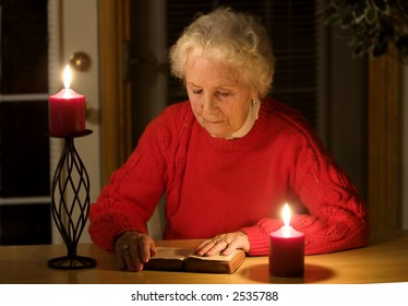 Elderly lady sitting in candlelight reading the bible during a power outage