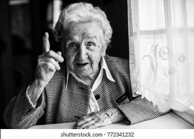Elderly lady speaks sitting at the table. Black and white portrait.