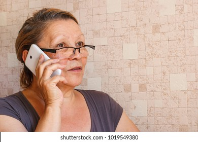 An elderly lady talking on a mobile phone