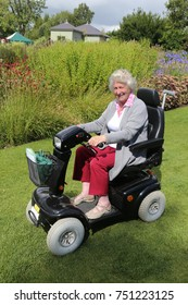 An elderly lady using a motor scooter to look around a garden