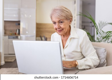 Elderly lady working with laptop. Portrait of beautiful older woman working laptop computer indoors. Senior woman using laptop at home, laughing