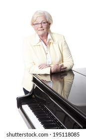 elderly lady in yellow leaning on grand piano in studio with white background