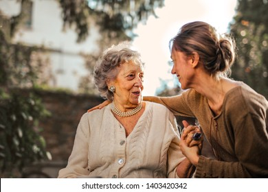 Elderly lady and a young woman holding each other's hand and smiling.