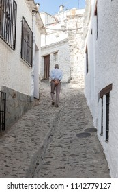 Elderly local man slowly climbing sloped street of Alpujarras town. Pampaneira, Granada, Spain