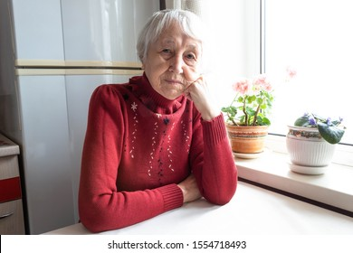 Elderly lonely woman depressed sitting at the table at home. Concept of quarantine, coronavirus Covid-19. Danger for old people