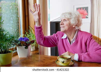 Elderly lonely woman saying goodbye to people outside