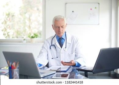 Elderly male doctor using his mobile phone and working on laptop while sitting at private clinic.