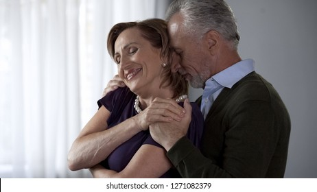 Elderly male hugging lady from behind, both smiling, harmonious marriage
