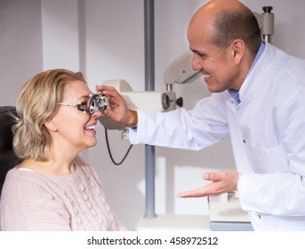 Elderly male optician examinating eyesight at the female pensioner
