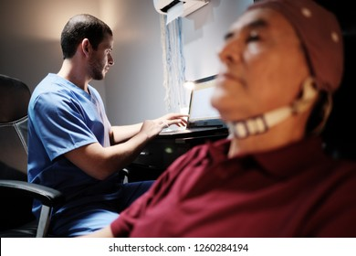 Elderly male patient with Alzheimer's illness, undergoing electroencephalogram examination Senior man with a nurse in clinic for medical evaluation using EEG. Brain illness prevention using technology